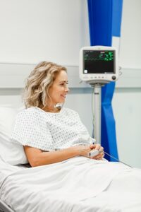 Mature female patient in hospital bed after spine rehabilitation